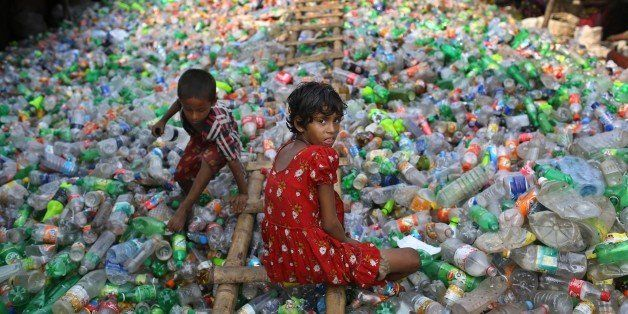 Bangladeshi girl Sharmin, 13 years old, looks into the camera as she works at a plastic recycling factory as a boy plays on a