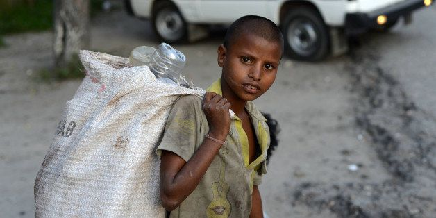 A young Indian ragpicker looka on as he collects used mineral water bottles in Siliguri on June 12, 2013, on World Day Agains