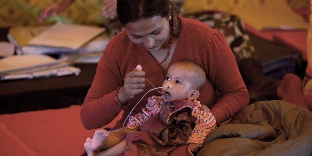 A Nepalese woman feeds her baby at the Nepali Military hospital in Kathmandu on April 29, 2015.  Israel sent some 250 soldier