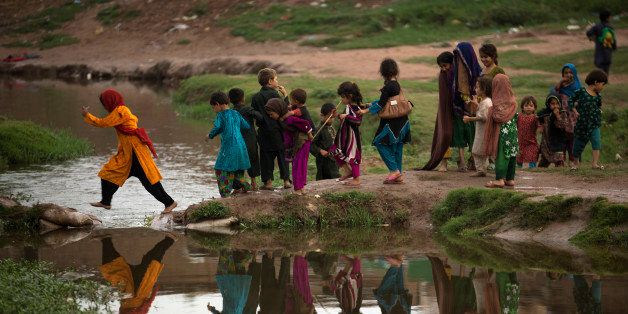 Children who are displaced from Pakistani tribal areas, where security forces are fighting against militants, cross a stream