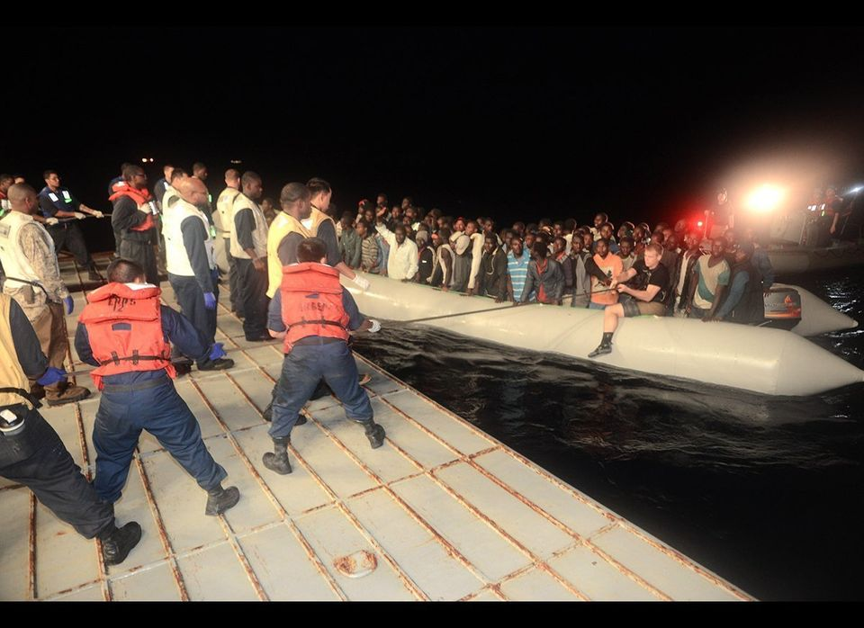 U.S. sailors aboard the USS Bataan embark a group of refugees and asylum seekers onto the ship in June of 2014. Bataan transf