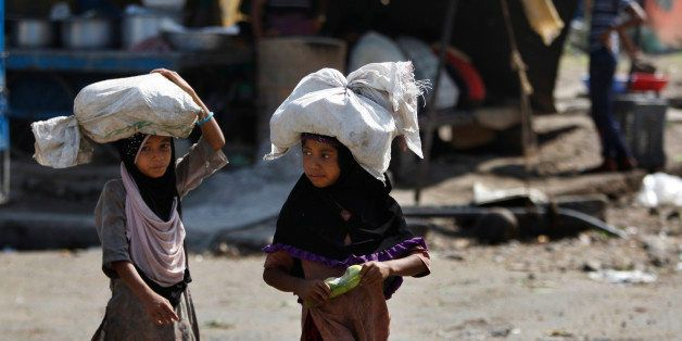 Indian child laborers carry sacks of vegetable leftovers collected from a wholesale market to be sold in their shantytown, on