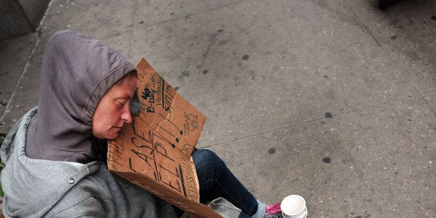 NEW YORK, NY - MAY 18:  A homeless woman rests while panhandling along Eighth Avenue in Manhattan on May 18, 2015 in New York