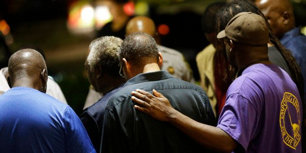 Worshippers gather to pray in a hotel parking lot across the street from the Emanuel AME Church following a shooting Wednesda
