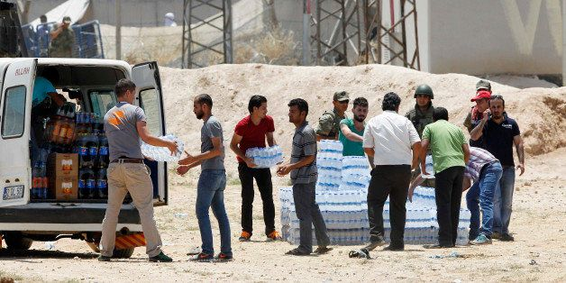 SANLIURFA, TURKEY - JUNE 15: Turkish aid workers carry bottles of water to the the Syrian refugees in Akcakale, on June 15, 2