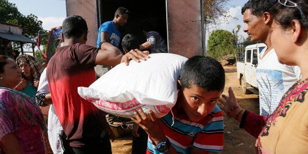 In this photo taken on Saturday, May 2, 2015, villagers, young and old, carry donated aid in the destroyed village of Pokhari
