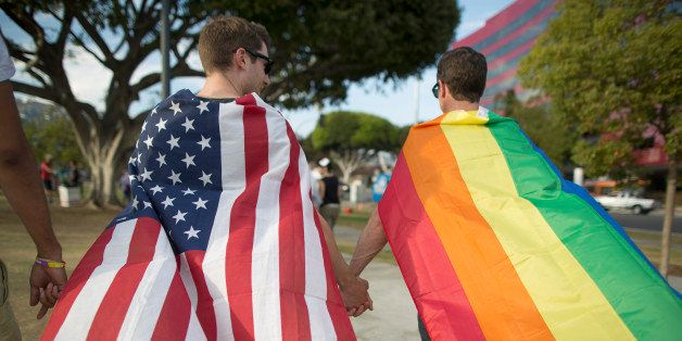 WEST HOLLYWOOD, CA - JUNE 26:  Robert Oliver and Mark Heller (R) hold hands, draped in flags, as they celebrate the Supreme C