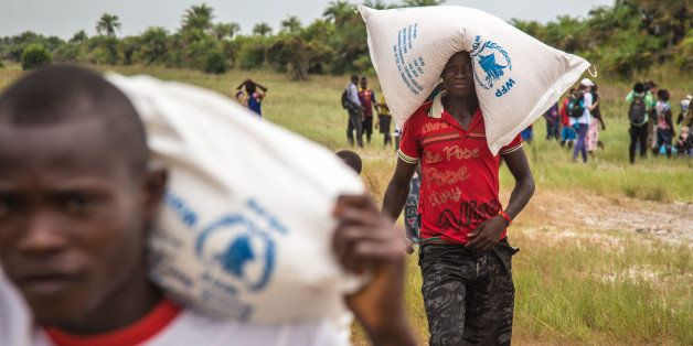People carry food aid from a British Navy helicopter after it made a food drop on Sherbro Island, Sierra Leone, Sunday, Dec.