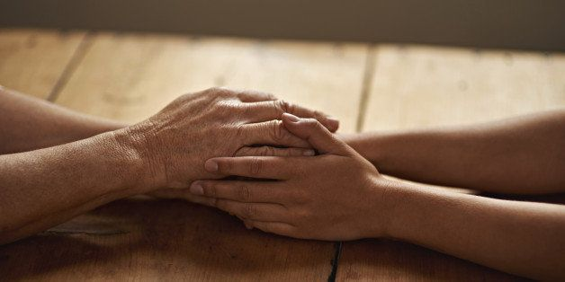 A cropped shot of a woman holding a loved one's hand in support