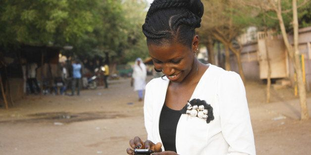 A smiling young woman writing a texto on her mobile phone.