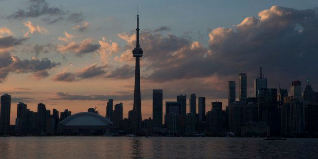 The sun sets over the Toronto skyline during the opening ceremony for the Pan Am Games, Friday, July 10, 2015. (AP Photo/Rebe