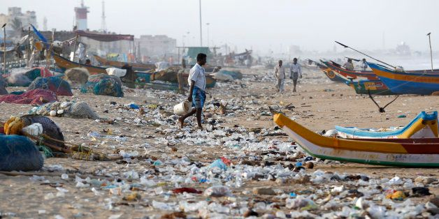 An Indian fisherman walks amidst, plastic and other garbage that got washed ashore on the Bay of Bengal coast in Chennai, India, Thursday, Aug.13, 2015. (AP Photo/Arun Sankar K)