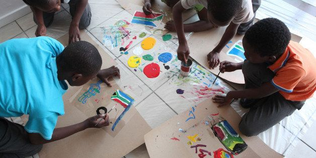 Local school children, start painting while attending an artists workshop at the Art Smart Brand center, in Alexandra Townshi