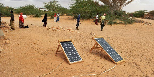 TO GO WITH STORY BY JEAN MARC MOJON Residents of the central Somali town of Wisil walk past solar panels laid out in front of