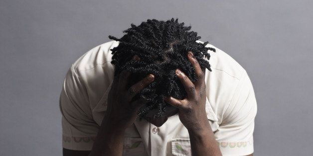 Black man, 20s, with head on hands looking frustrated