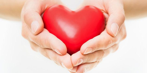 Female Hands presenting a red heart.