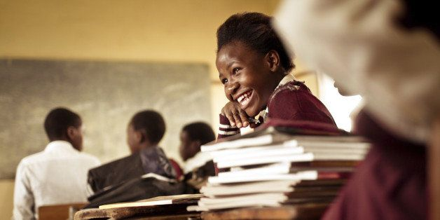 A Happy young South African girl (from the Xhosa tribe) works on her studies and jokes with her friends at at an old worn des