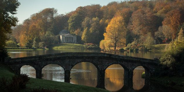 STOURHEAD, ENGLAND - NOVEMBER 02:   The sun shines on trees that are displaying their autumn colours surrounding the Palladia