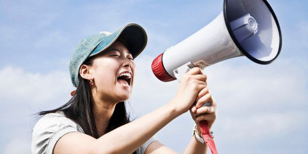 portrait of young japanese woman shouting through megaphone