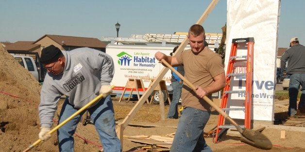 U.S. Army Staff Sgt. Kelly H. Johnson, left, and Sgt. Christopher F. King, both of the 188th Engineer Company, shovel sand in