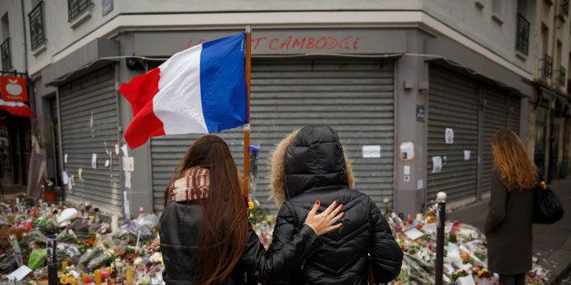 Two women stand outside the Petit Cambodge restaurant, a site of last Friday's attacks, in Paris, Tuesday, Nov. 17, 2015. Fra