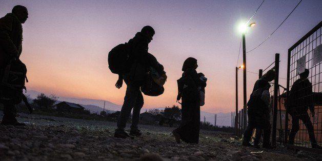 Migrants and refugees enter a registration camp after crossing the Greek-Macedonian border near Gevgelija on November 17, 201