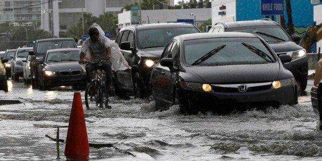 A cyclist and vehicles negotiate heavily flooded streets as rain falls, Tuesday, Sept. 23, 2014, in Miami Beach, Fla. Certain