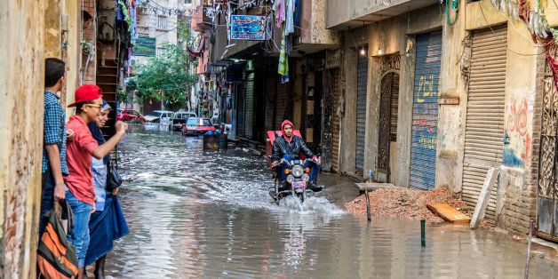 An motorcyclist rides through floodwater after a heavy rainfall in the coastal city of Alexandria, Egypt, Sunday, Oct. 25, 20