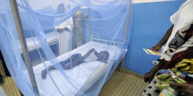 A sick child lays under a mosquito net in a hospital on April 24, 2015 in the popular suburb of Port-Bouet in Abidjan, on the