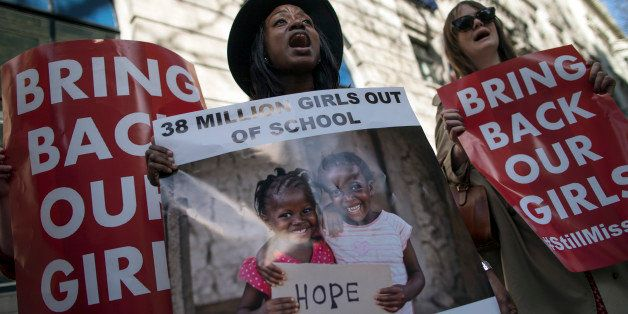 LONDON, ENGLAND - APRIL 14:  Women hold a signs as other protesters gather outside Nigeria House to mark the one year anniver