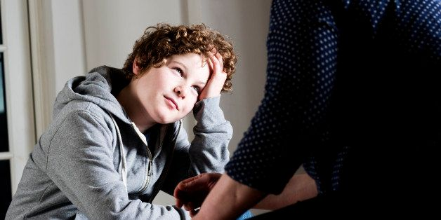 'Eleven year old boy talking to a parent,guardian or social worker.'