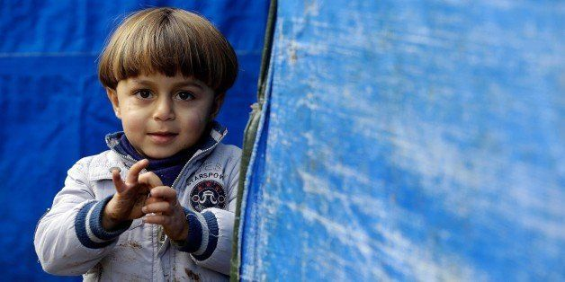 LEBANON, BEIRUT - DECEMBER 31: A Syrian child one of those who have been forced to leave their homes because of the war in their country since 2011, stands outside a makeshift tent at the Al Hayat and Al Nour refugee camp in Cabal Lebanon region, Lebanon on December 31, 2015. As the weather cools down, Syrian refugees struggle to survive heavy winter conditions at the tent city. (Photo by Ratib Al Safadi/Anadolu Agency/Getty Images)