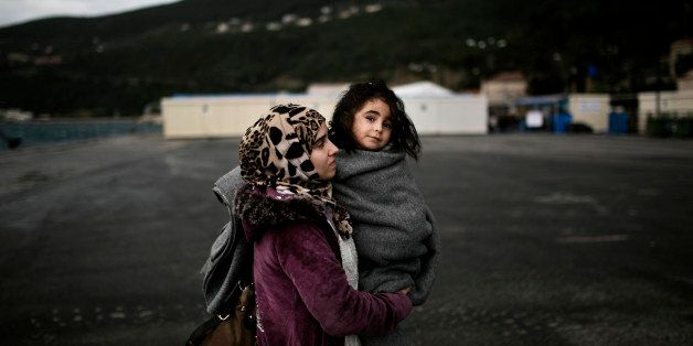 A woman from Syria holds her baby as she arrives at the registration centre on the Greek island of Samos, after being rescued