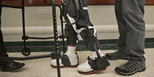 James Cody, 29, center, walks with the aid of a bionic exoskeleton and physical therapists at the Burke Rehabilitation Center