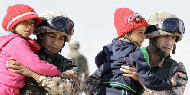 TOPSHOT - Jordanian security forces help Syrian girls after crossing from Syria into Jordan, at the Hadalat border crossing,