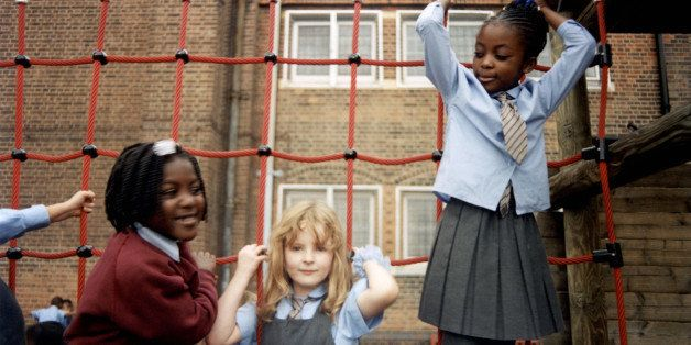 Group of school kids playing on a wooden climbing frame, South London, UK, 2000s. (Photo by: PYMCA/UIG via Getty Images)