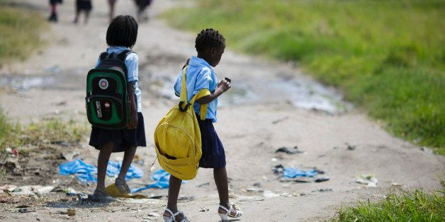 Beira, Mozambique - September 28: Girls with backpacks walk along a path on September 28, 2015 in Beira, Mozambique. (Photo b