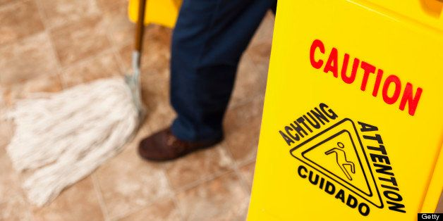 Service Industry:  Caution sign and man mopping retail store floor