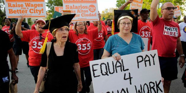 A woman carries a sign for equal pay as she marches with other protestors in support of raising the minimum wage to $15 an ho