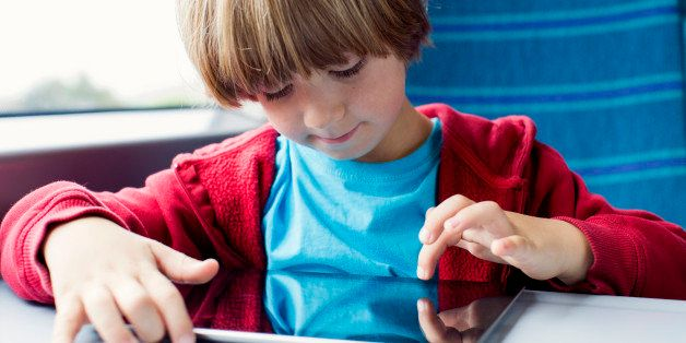 Young boy uses his tablet whilst travelling by train