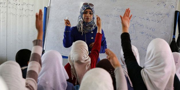Syrian refugee children raise their hands as they attend class in a UNICEF school at the Al Zaatari refugee camp in the Jorda