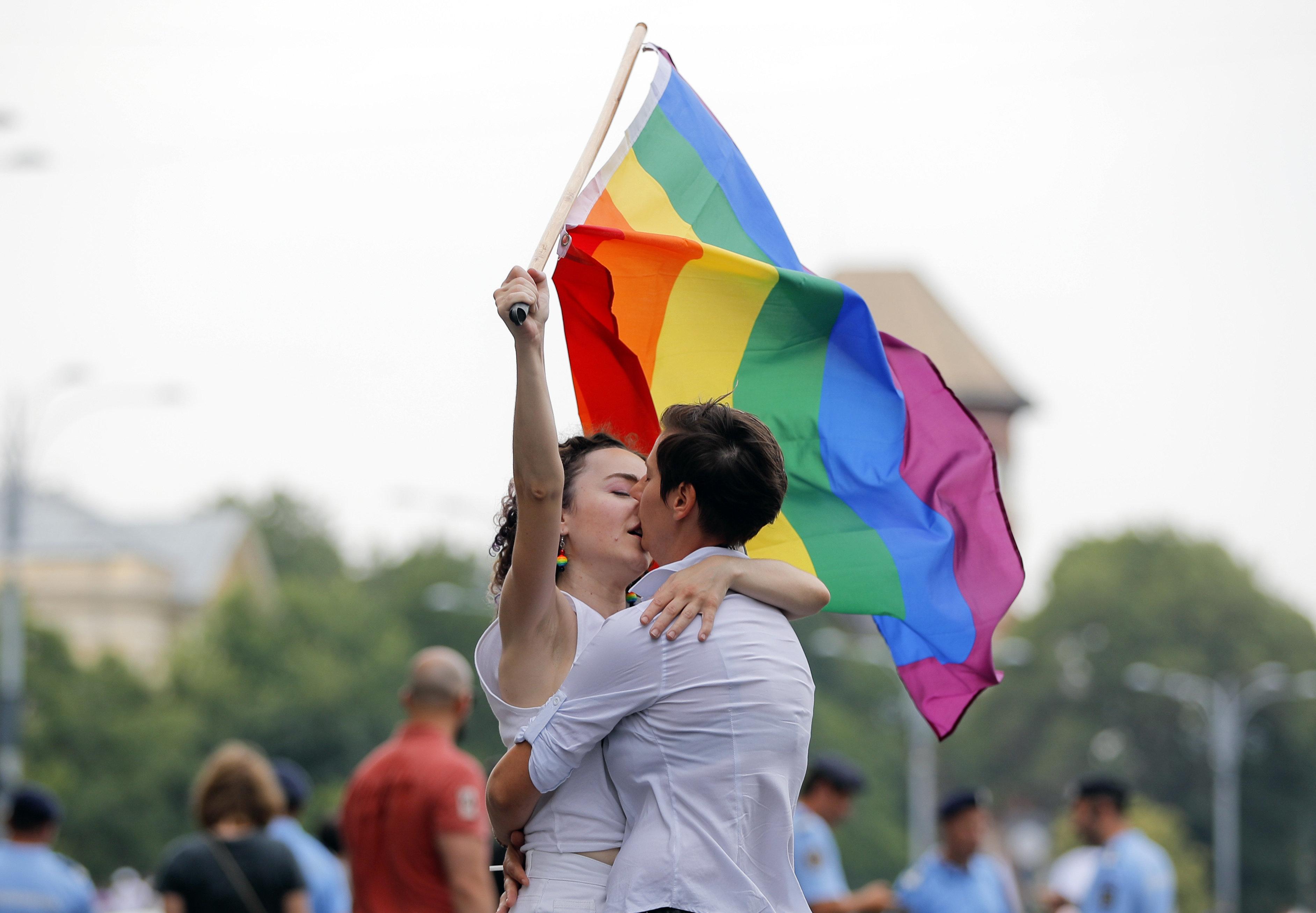 루마니아 부쿠레슈티에서 열린 프라이드 퍼레이드에서 두 여성이 레인보우 깃발을 손에 든 채 키스하고 있다. 2018년 6월9일.