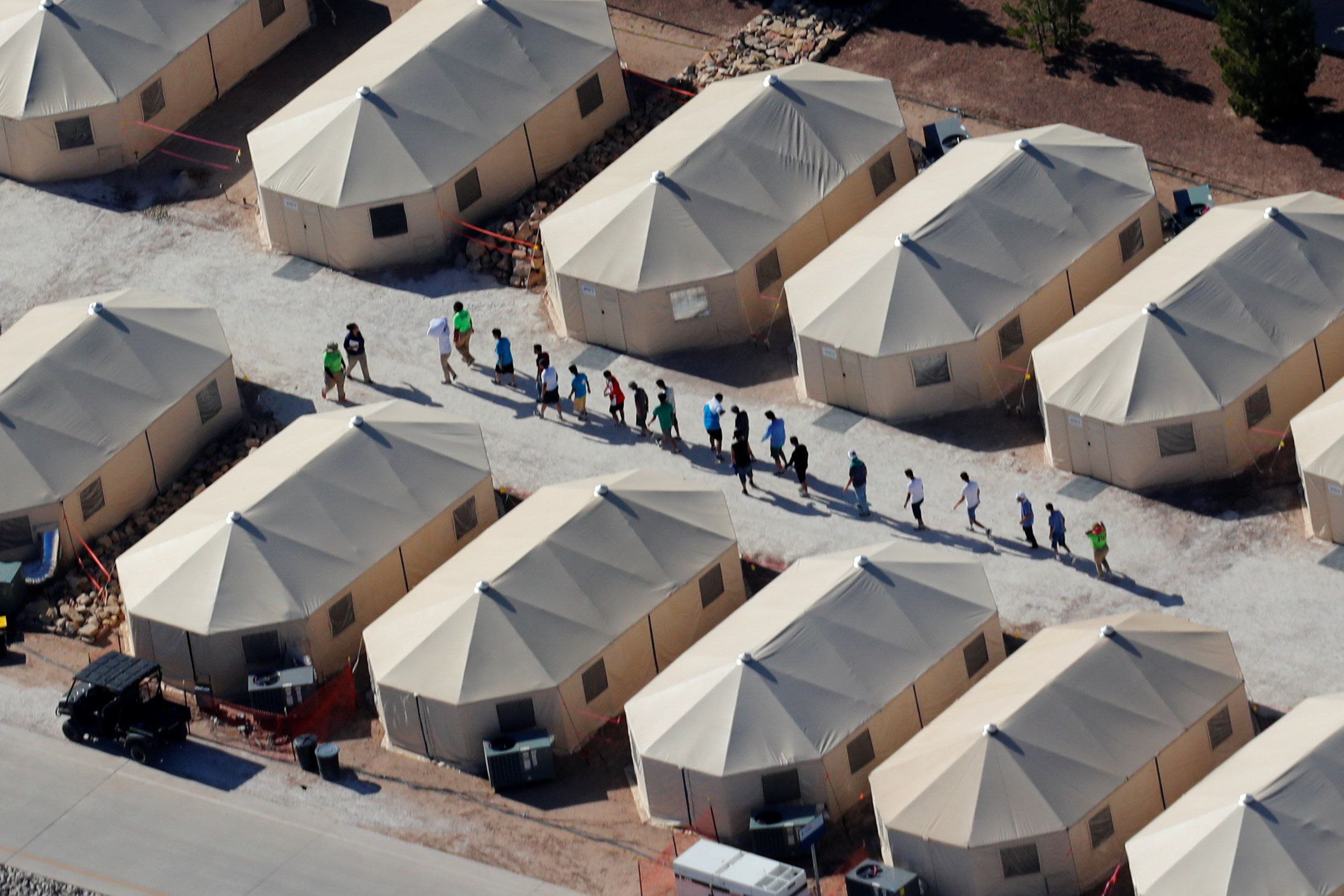 Immigrant children shown walking in single file at the Tornillo, Texas, tent city on June 19, 2018.