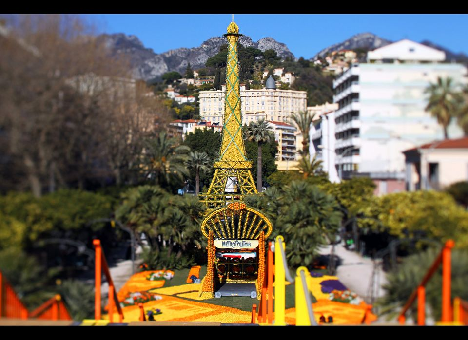A picture taken with a tilt and shift lens shows sculptures made with oranges and lemons representing the Eiffel tower and th