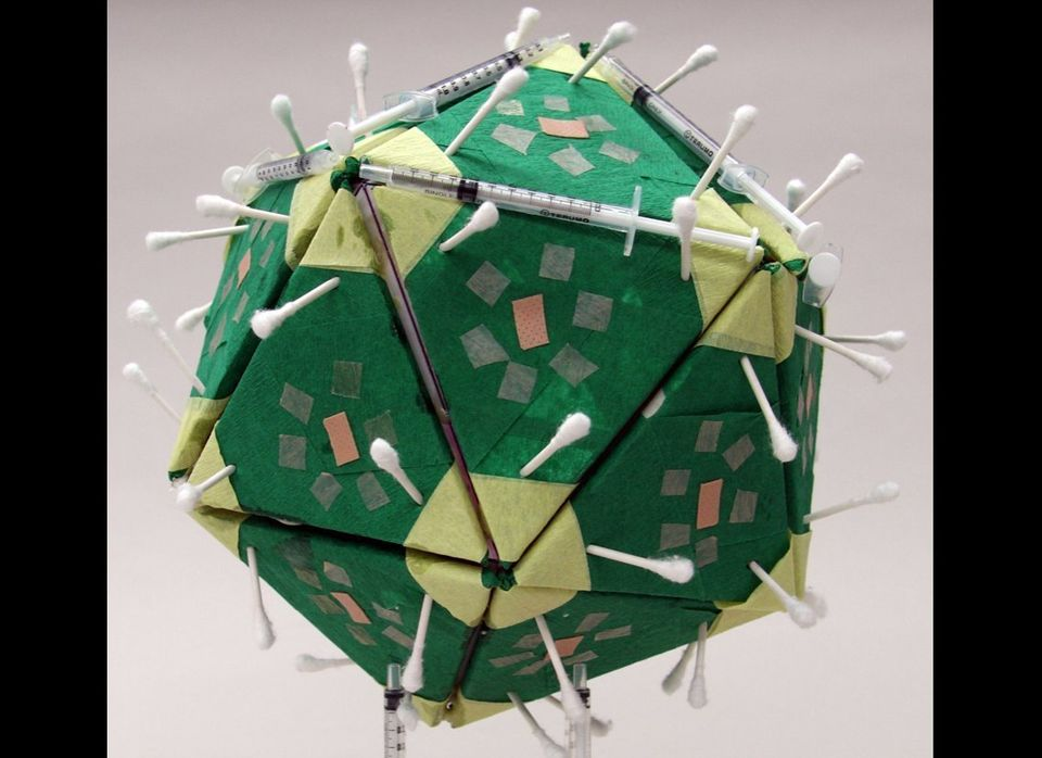 Angela Cesena, Model of Papillomavirus, 2011.  Cardboard, yellow and green crepe paper, plastic syringes,  Q-Tips, and Band