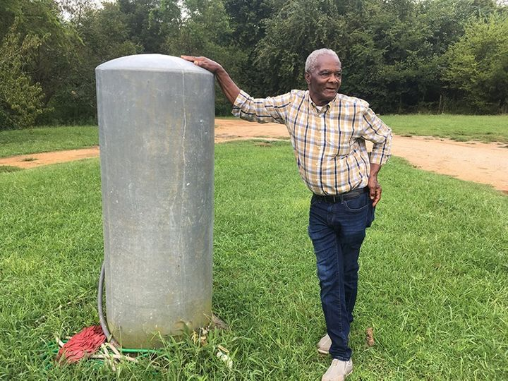 Booker Gipson leans against the tank his family uses for water. The 77-year-old grandfather is concerned the landfill across