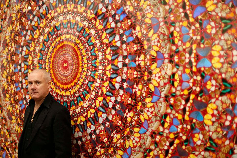 "British artist Damien Hirst stands beside the 2006 piece ""I Am Become Death, Shatterer of Worlds"", butterflies and household"