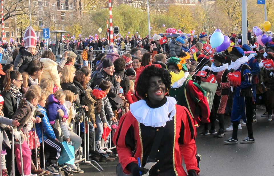 "Crowds of people await the arrival of St. Nicholas, or Sinterklaas, on his horse as some of his helpers named ""Zwarte Piet"" w"