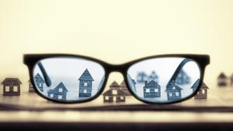 Eyeglasses lie on the open newspaper with paper houses. That could mean rent, search, purchase real estate.