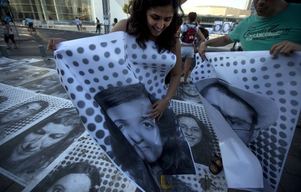 Israelis hold their pictures taken by French street artist JR in Tel Aviv at the site of a tent camp set up to protest agains